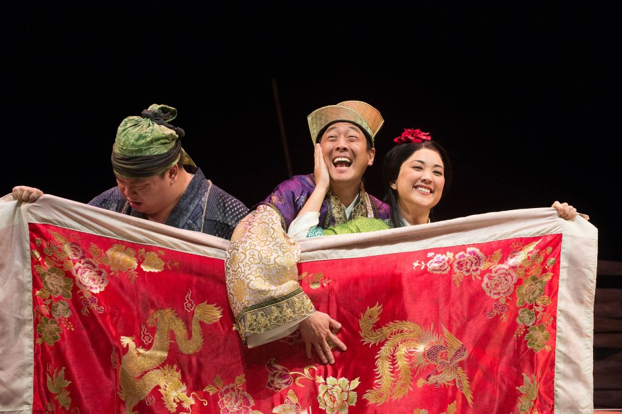 Master Yuan (Paul Juhn, center) and Blossom (Leah Anderson) have some fun behind the blanket, unbeknownst to Blossom's husband Tao (Eugene Ma, left). Photo: Jenny Graham.